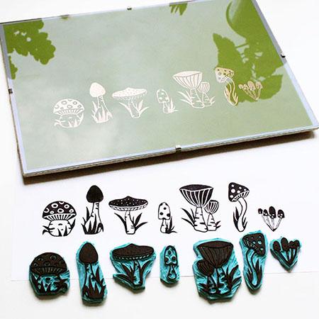 Handgeschnitzte Stempel mit Pilzmotiven, dazu zwei Drucke mit schwarzer Tinte und mit Goldpuder
