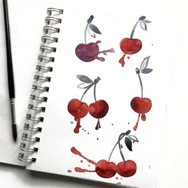 Kirschen, die mit Aquarellfarben in ein Skizzenbuch gemalt wurden.