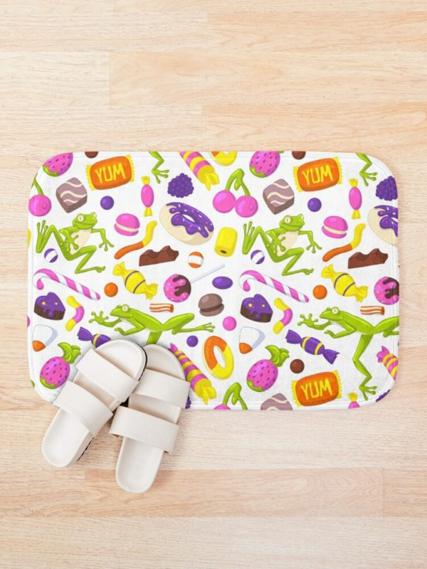 Bath rug printed with a pattern of different sweets and light green frogs.