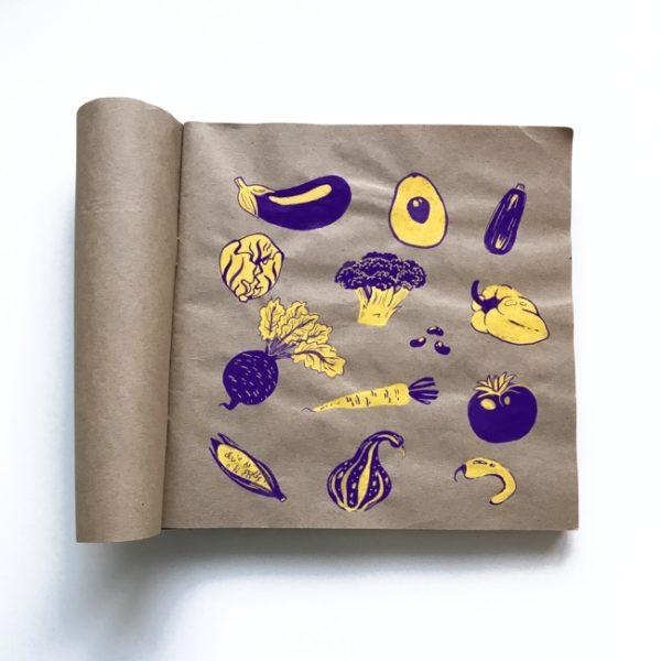 Gelb-lila-farbenes Gemüse auf braunem Papier.